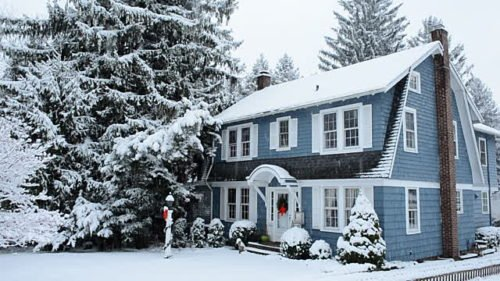 Blue house covered in snow after a large snow fall